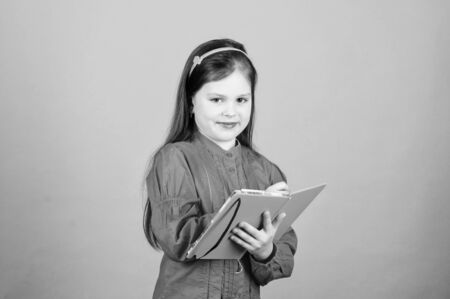 Lets look in the book of scientific knowledge. Cute little child writing knowledge test report. Adorable small girl holding book knowledge in hands. Knowledge day or September 1 Stok Fotoğraf - 129811231