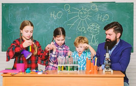 kids in lab coat learning chemistry in school laboratory. chemistry lab. happy children teacher. back to school. making experiment in lab or chemical cabinet. Research and development