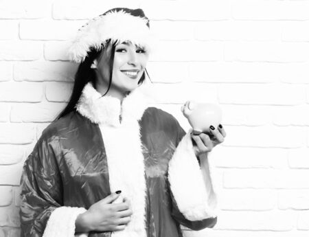 pretty cute sexy santa girl or smiling brunette woman in new year sweater and christmas or xmas hat holds pink piggy pig bank on white brick wall backgroun