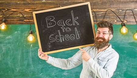 Teacher in eyeglasses holds blackboard with title back to school. Hiring teachers concept. Man with beard and mustache on happy face welcomes colleagues, chalkboard on background