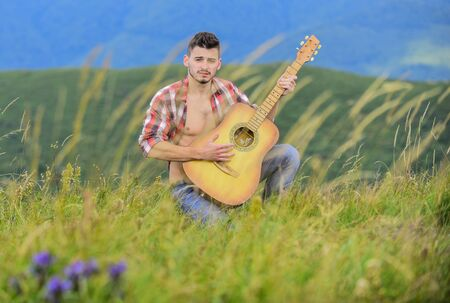 Summer music festival outdoors. Playing music. Sound of freedom. Inspired musician play rock ballad. Compose melody. Inspiring environment. Man with guitar on top of mountain. Acoustic music
