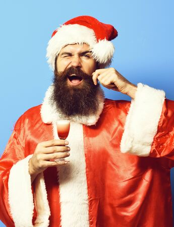 handsome bearded santa claus man with long beard on funny face holding glass of alcoholic shot in christmas or xmas sweater and new year hat and touching mustache on blue studio backgroun