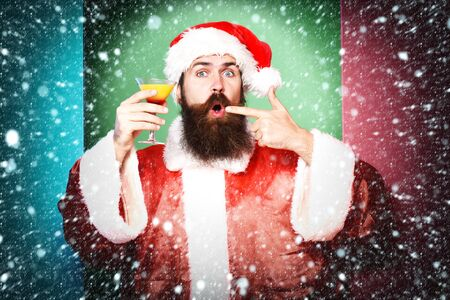 handsome bearded santa claus man with long beard on funny face holding glass of alcoholic beverage in christmas or xmas sweater and new year hat shows on it on colorful studio backgroun