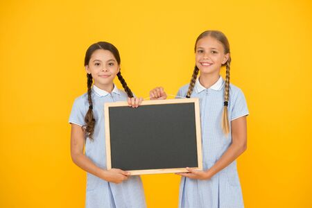 True information. Little girls hold writing surface yellow background. Children and chalkboard for writing information. Blank board for information. Fresh school information copy space. School news