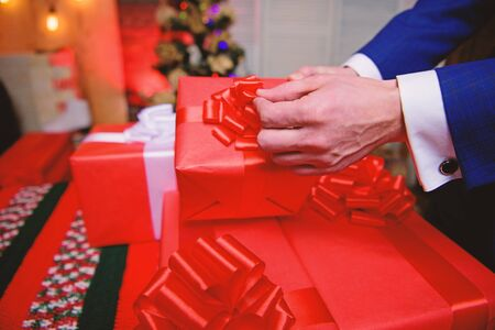 Wrapping gifts concept. Magic moments. Prepare surprise gifts for family and friends. Gift boxes with big ribbon bow close up. Red wrapped gifts or presents. Prepare for christmas and new year.