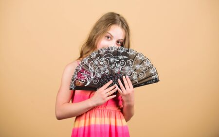 Dances with fan. Girl fanning herself with fan. Air circulation. Art and culture. Handheld fan create airflow. Airflow from handfans increases evaporation. Cooling effect. Folding fans. Acting school Foto de archivo