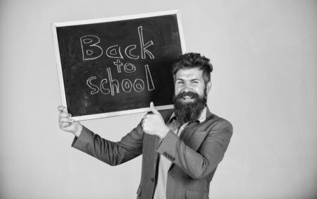 Teacher bearded man stands and holds blackboard with inscription back to school grey background. Teacher advertises back to studying, begin school year. Invite to celebrate day of knowledge Stock Photo