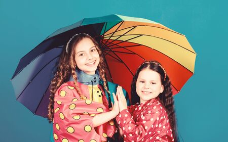 rain protection. Rainbow. autumn fashion. happy little girls with colorful umbrella. cheerful hipster children, sisterhood. family bonds. Little girls in raincoat. Any weather is good Reklamní fotografie