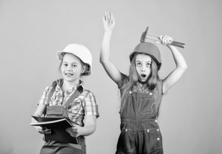 Little kids in helmet with tablet and hammer. Labor day. 1 may. small girls repairing together in workshop. Foreman small girls inspector. Repair. happy children. Future career. small girls Foto de archivo