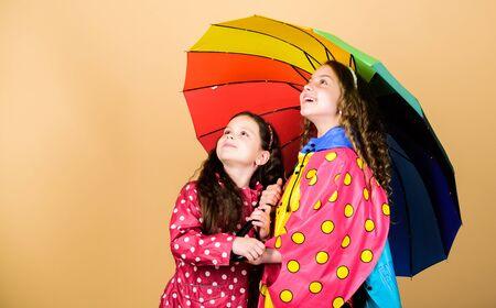 family bonds. Little girls in raincoat. autumn fashion. cheerful hipster children, sisterhood. rain protection. Rainbow. happy little girls with colorful umbrella. Feeling comfortable