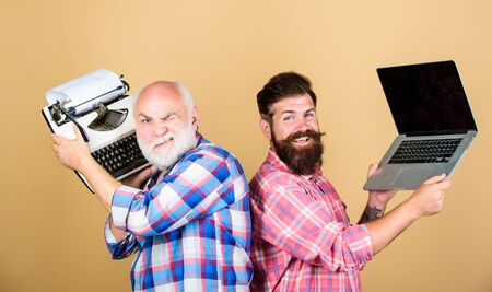 Modern life and remnants of past. Digital technologies. Battle of technologies. Old generation. Senior man with typewriter and hipster with laptop. Master new technologies. Men work writing devices 스톡 콘텐츠
