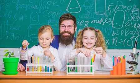 Research studies. Science teacher and pupils doing research work. Teacher and primary school children holding test tubes in research laboratory. Experimental research is conducting a laboratory test