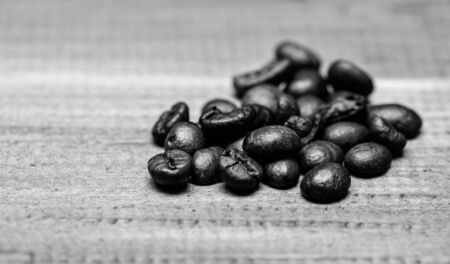 Coffee for inspiration and energy charge. Texture and background concept. Coffee shop or store. Fresh roasted coffee close up. Pile beans on blue wooden background. Degree of roasting coffee beans