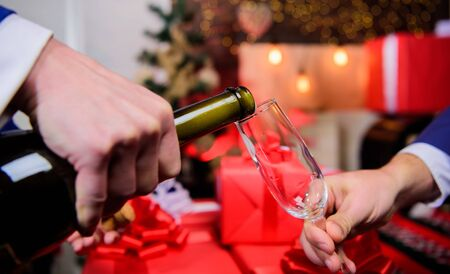 Hands pouring champagne into elegant glass christmas decorations background. Cheers concept. Last minute before new year. Drink champagne or sparkling wine. Celebrate new year with champagne