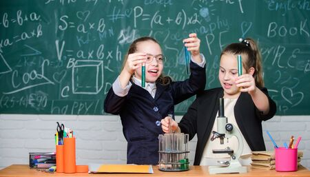 Make studying chemistry interesting. Educational experiment concept. Girls classmates study chemistry. Microscope and test tubes on table. Perform chemical reactions. Basic knowledge of chemistry Banque d'images