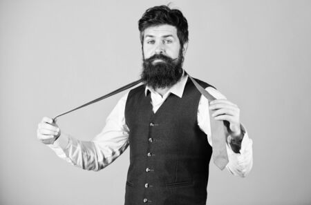 Start with your collar up and the tie around your neck. Art of manliness. Man bearded hipster try to make knot. Different ways of tying necktie knots. How to tie necktie. How to tie simple knot Archivio Fotografico