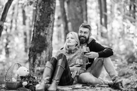 Couple in love celebrate anniversary picnic date. Couple cuddling drinking wine. Enjoying their perfect date. Happy loving couple relaxing in park together. Romantic picnic with wine in forest