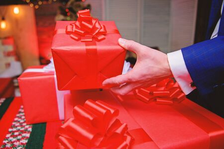 Prepare surprise gifts for family and friends. Gift boxes with big ribbon bow close up. Red wrapped gifts or presents. Prepare for christmas and new year. Wrapping gifts concept. Magic moments.