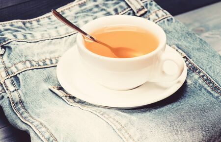 Healthy habits. Tea time concept. Cup mug hot water and bag of tea. Process tea brewing in ceramic mug. Herbal green or black whole leaf. Mug filled boiling water and tea bag on blue jeans background. Imagens