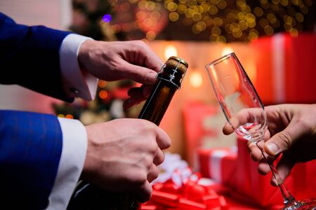 Celebrate new year with champagne. Hands opening champagne bottle and hold glass christmas decorations background. Last minute before new year. New year countdown. Drink champagne or sparkling wine.