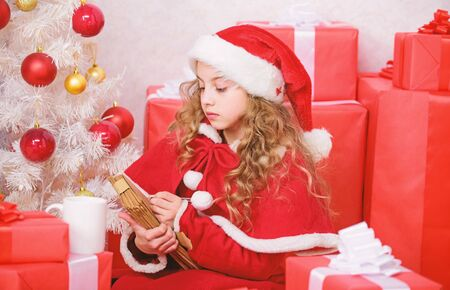 Girl hold pen and paper near christmas tree and gift box. Believe in miracle. Send letter for santa. Wish list. Child santa costume enjoy christmas eve. Child write letter to santa claus. Dear santa