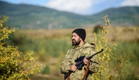 Hunter hold rifle. Bearded hunter spend leisure hunting. Focus and concentration of experienced hunter. Hunting and trapping seasons. Hunting masculine hobby. Man brutal gamekeeper nature background