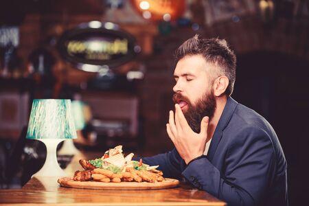 Der Mann erhielt eine Mahlzeit mit gebratenem Kartoffelfischstäbchenfleisch. Er verdient leckeres Essen. Guten Appetit. Kalorienreicher Snack. Leckeres Essen. Entspannen Sie sich nach einem harten Tag. Anzug des Geschäftsmannes sitzen im Restaurant Standard-Bild