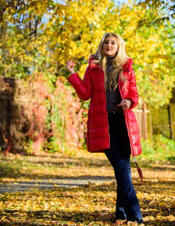 Autumn season fashion. Girl enjoy autumn walk. Clothing for autumn walk. Woman wear coat or warm jacket while stand in park yellow foliage background. Must have fall wardrobe. Be bright this autumn