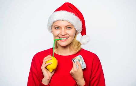 Rich girl with lemon and money. Woman lemon millionaire. Lemon money concept. Girl santa hat drink juice lemon straw while hold pile of money. Symbol of wealth and prosperity. Christmas wishes