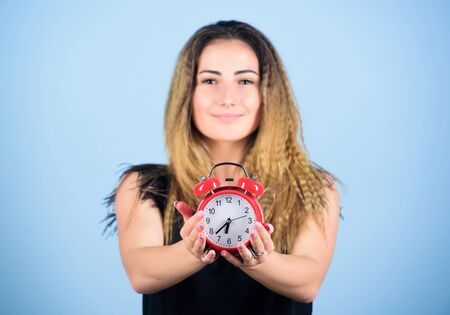 Pretty girl managing her time. Woman hold red alarm clock. Counting time till deadline. Overwork or being late. It is time. Watch repair. Few minutes. Time management. Punctuality and discipline Stock Photo