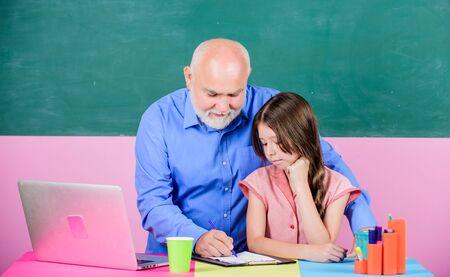 Senior teacher and girl at school lesson. Modern teaching method. Student girl with teacher man at blackboard. Schoolgirl and tutor with laptop. Modern knowledge. Modern education. Happy student