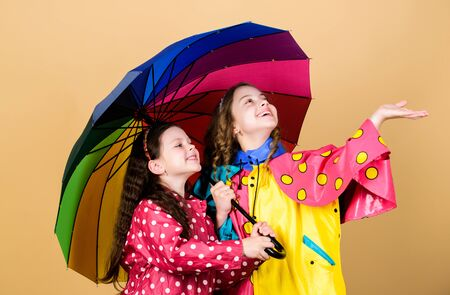 Kids girls happy friends under umbrella. Rainy weather with proper garments. Bright umbrella. It is easier to be happy together. Be rainbow in someones cloud. Rainy day fun. Happy walk under umbrella