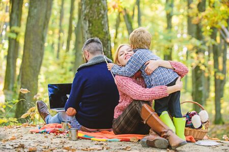 Happy son with parents relax in autumn forest. Mother, father love their little boy child. Fall weather. Wine or coffee drinking. Spring mood. Happy family day. Family picnic. Easter celebrate