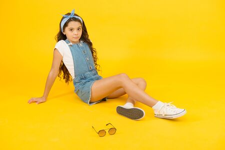She is really cute. Adorable baby girl relax on yellow background. Brunette girl with long wavy hair in casual style. Cute little girl of fashion. Small girl with beauty look 免版税图像