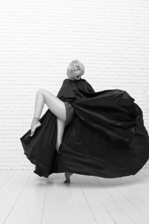 Fancy look. Sensual woman wearing yellow hair wig and black toga with fashion look. Sexy look of fashion model. Playful girl having fun with crazy look on white brickwall Banque d'images - 131299619