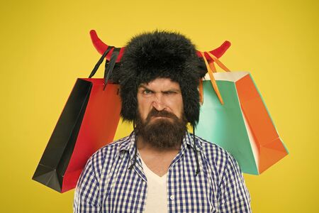 Dissatisfied with purchase. Unhappy hipster with his purchase in paperbags hanging on bull horns. Brutal bearded man with personal purchase. Buying fashion purchase