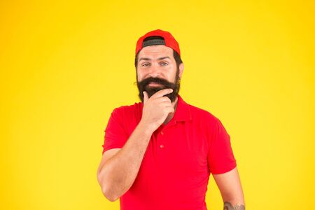 Nice thought. Salesman career. Hiring shop store worker. Hospitality staff. Supermarket staff wanted. Man thoughtful bearded hipster with mustache wear uniform yellow background. Shop staff concept Imagens