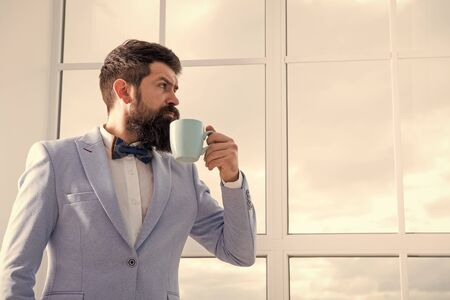 Man groom drinking coffee early in morning. Beginning of great day. Important day in his life. Get ready. Enjoy every minute. Hipster in tuxedo with bow tie making sip of coffee. But first coffee Stock Photo