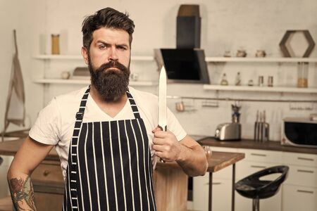 Kitchen equipment. culinary business. tasty cuisine. serious and confident chef in restaurant. bearded man hipster in kitchen with knife. brutal man in cook apron. mature male with beard cooking Фото со стока