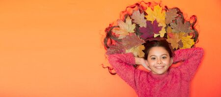 Im hairdresser. Happy girl with colorful leaves in hair. Small child in autumn mood on brown background. Hair salon. Hairdressers salon or parlor. Kids barber. Beauty salon. Hairdressing, copy space Stock Photo