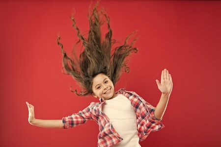 Amazing long hair. Cute small girl with long hair curls waving on red background. Adorable little child taking care of long brunette hair. Enjoying long curly hairstyle