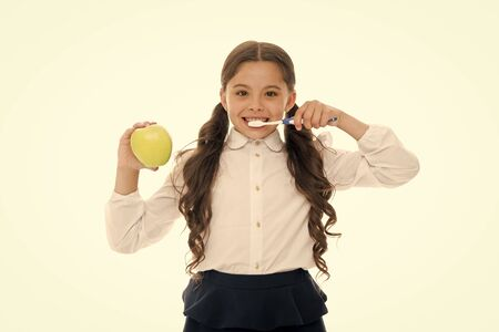 Brush teeth every day. Oral hygiene concept. Girl hold toothbrush and apple white background. Child girl hold fruit and brush tooth with paste. Child schoolgirl kid happy care tooth oral hygiene