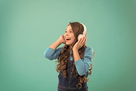 Music sounds better with my headphones. Little girl wearing headphones on blue background. Cute child listening to music in ear stereo headphones. Adorable small kid wearing modern headphones