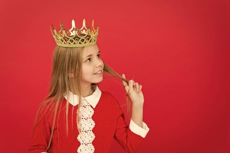 Childhood happiness. family and love. childrens day. Good parenting. Child care. small girl child. School. happy little girl on red background. littlle miss in crown. copy space. Feeling playful Фото со стока