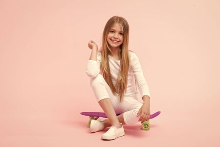 Enjoying vibes on penny board. Cute little child sitting on penny board deck on pink background. Adorable girl skater with violet penny board. Small skateboarder with penny skateboard 스톡 콘텐츠