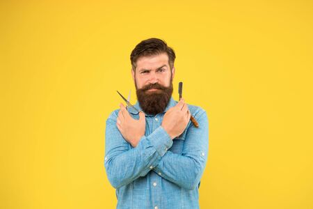 Skilled at cutting hair. Professional barber in hair salon. Brutal hipster with mustache and beard hair hold shaving tools. Bearded man ready to cut hair with scissors and razor. Barbershop
