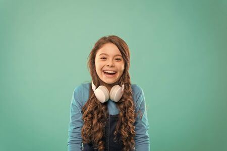 Drift into the music. Happy little DJ on blue background. Cute girl smiling with DJ headphones. Small child using wireless headset for DJ disco. Adorable kid enjoying DJ tune playing in radio