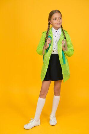 Rain is not hindrance. Waterproof cloak. Schoolgirl wear green raincoat going to school. Waterproof fabric for your comfort. Rainproof accessory. Waterproof clothes. Kid girl happy wear raincoat