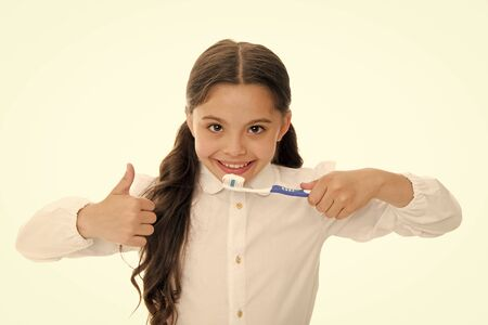 Brush teeth every day. Oral hygiene concept. Girl hold toothbrush and show thumbs up gesture white background. Child girl brush tooth with paste. Child schoolgirl kid happy care tooth oral hygiene