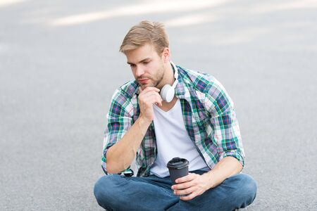 More coffee. coffee to go. guy drink coffee outdoor. man sit on ground. tired student in headset. online education. listen music. ebook concept. man checkered shirt. student relax and recharge